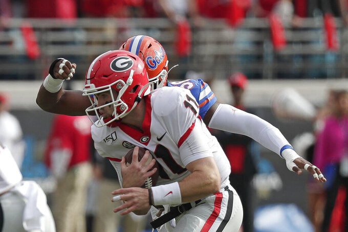 Georgia quarterback Jake Fromm, left, scrambles for yardage before he is brought down by Florida linebacker Jonathan Greenard during the first half of an NCAA college football game, Saturday, Nov. 2, 2019, in Jacksonville, Fla. (AP Photo/John Raoux)