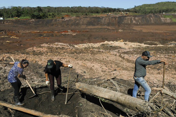 Tereza Ferreira Nascimento, center, her sister-in-law Sonia Santos, left, and her brother Pedro Ferreira dos Santos dig with garden tools in search of the body of Tereza's and Pedro's missing brother Paulo Giovane Santos, days after a mining company's dam collapsed in Brumadinho, Brazil, Wednesday, Jan. 30, 2019.