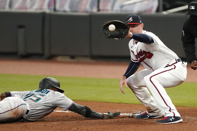 Miami Marlins' Lewis Brinson (25) dives back to first base ahead of the throw to Atlanta Braves first baseman Freddie Freeman (5) in the fourth inning of a baseball game Wednesday, Sept. 23, 2020, in Atlanta. (AP Photo/John Bazemore)