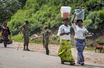 Two women heading towards Congo carry food on their heads as they walk past Ugandan army soldiers ensuring those crossing the border do not do so without being screened for symptoms of Ebola, at the Mpondwe border crossing to Congo, in western Uganda Friday, June 14, 2019.  In Uganda, health workers had long prepared in case the Ebola virus got past the screening conducted at border posts with Congo and earlier this week it did, when a family exposed to Ebola while visiting Congo returned home on an unguarded footpath. (AP Photo/Ronald Kabuubi)