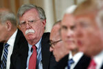 FILE - In this April 18, 2018 file photo, National security adviser John Bolton, left, listens to President Donald Trump, far right, speak during a working lunch with Japanese Prime Minister Shinzo Abe at Trump' s private Mar-a-Lago club in Palm Beach, Fla. Also at the meeting are from left, White House chief economic adviser Larry Kudlow, third left, and Vice President Mike Pence, second left. Trump has fired national security adviser John Bolton. Trump tweeted Tuesday that he told Bolton Monday night that his services were no longer needed at the White House.  (AP Photo/Pablo Martinez Monsivais)
