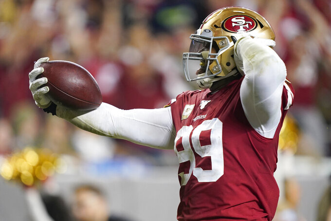 San Francisco 49ers defensive tackle DeForest Buckner (99) scores a touchdown against the Seattle Seahawks during the second half of an NFL football game in Santa Clara, Calif., Monday, Nov. 11, 2019. (AP Photo/Tony Avelar)