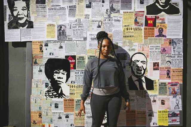 Artist Jannah Williams poses in front of a mixed-media piece at Nomad Bar in Wilmington, Del., on Nov. 4, 2020.   Williams worked for several days, creating a stunning mixed-media piece that uses newspaper clips and old racist fliers as a base; on top are paintings of the faces of people who matter in this moment. They include civil rights leader Martin Luther King, Jr.; the first Black woman elected to the U.S. Congress, Shirley Chisholm; and former President Barack Obama. Ahmaud Arbery, who was shot to death while jogging in Georgia earlier this year, and Breonna Taylor, who was killed by police in Kentucky in her home, also are included. (Joe del Tufo/Moonloop Photography via AP)