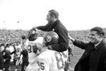 FILE - In this Nov. 20, 1965, file photo, Michigan State ends Charles Smith, left, and Bob Viney (85) hoist defensive coach Henry Bullough as the victorious Spartans left the field after beating Notre Dame, 12-3, in South Bend, Ind. Henry Bullough, whose play and coaching on the football field at Michigan State put him in its athletics hall of fame, has died. He was 85.  Chuck Bullough, one of his sons, is an assistant coach for the Spartans under Mark Dantonio and the school announced his death Monday, Nov. 25, 2019. (AP Photo/File)