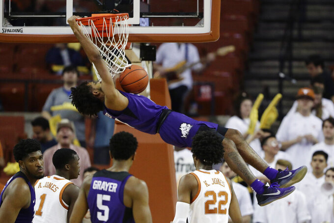 TCU guard PJ Fuller (4) hangs on the rim as he scores against Texas during the second half of an NCAA college basketball game in Austin, Texas, Wednesday, Feb. 19, 2020. (AP Photo/Eric Gay)