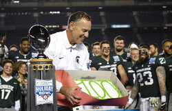 "FILE - In this Dec. 28, 2017, file photo, Michigan State coach Mark Dantonio holds a cake with ""100"" written on it after Michigan State defeated Washington State 42-17 in the Holiday Bowl NCAA college football game in San Diego. It was Dantonio's 100th win to close his 11th season and his school-record fifth bowl. Dantonio announced his retirement Tuesday, Feb. 4, 2020, ending a 13-year run in which he guided the Spartans to heights they hadn't reached in decades. (AP Photo/Denis Poroy, File)"