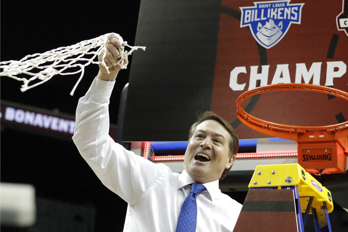 Saint Louis coach Travis Ford waves the net after Saint Louis defeated St. Bonaventure during an NCAA college basketball game in the final of the Atlantic 10 men's tournament Sunday, March 17, 2019, in New York. Saint Louis won 55-53. (AP Photo/Julio Cortez)