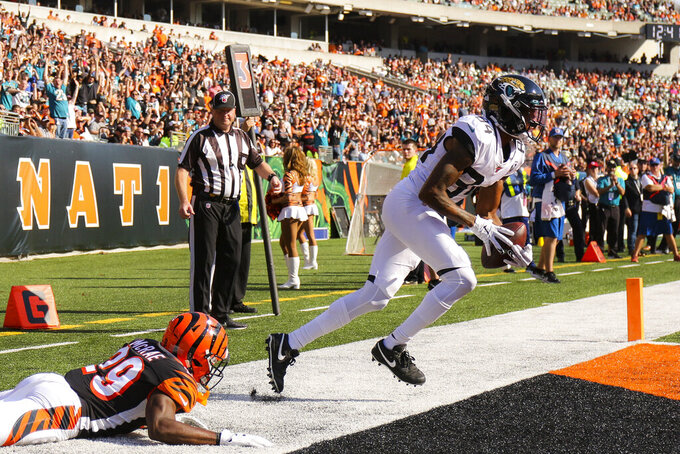Jacksonville Jaguars wide receiver Keelan Cole (84) scores a touchdown against Cincinnati Bengals outside linebacker Nick Vigil (59) in the second half of an NFL football game, Sunday, Oct. 20, 2019, in Cincinnati. (AP Photo/Gary Landers)