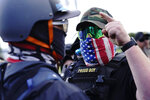 A right-wing demonstrator, right, gestures toward a counter protester as members of the Proud Boys and other right-wing demonstrators rally on Saturday, Sept. 26, 2020, in Portland, Ore.About 200 people gathered in Portland, for a right-wing rally, dozens of them wearing militarized body armor. It was far fewer than the thousands expected to appear. (AP Photo/John Locher)