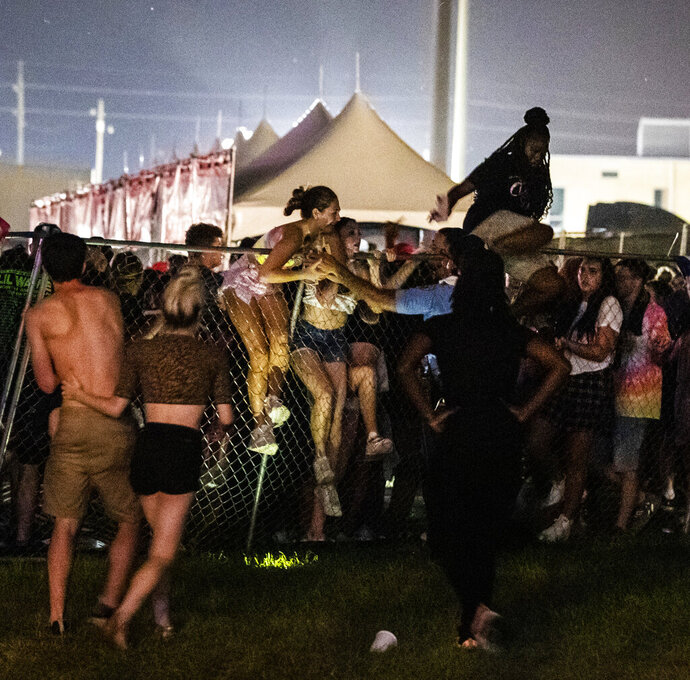 In this  Saturday, Sept. 7, 2019 photo, Festival-goers try to escape the crowd during Lil Wayne's fifth annual Lil WeezyAna Fest at the UNO Lakefront Arena grounds in New Orleans. A crowd stampede injured several people attending a New Orleans festival organized by rapper Lil Wayne. (Sophia Germer/The Advocate via AP)