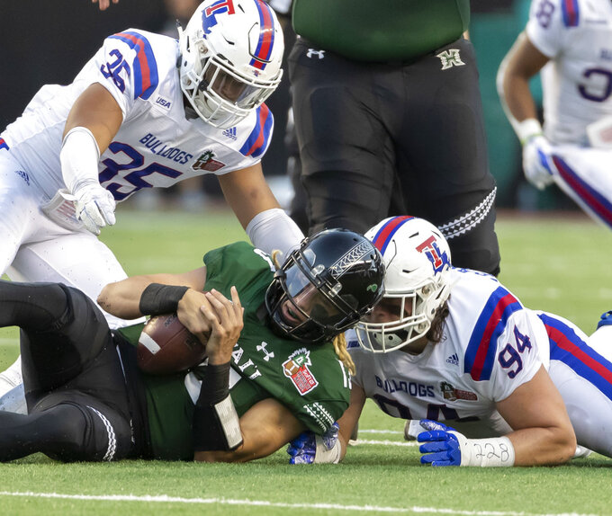 Hawaii quarterback Cole McDonald (13) recovers his own fumble while being tackled by Louisiana Tech linebacker Collin Scott (35) and defensive tackle Jordan Bradford (94) in the first half of the Hawaii Bowl NCAA college football game, Saturday, Dec. 22, 2018, in Honolulu. (AP Photo/Eugene Tanner)