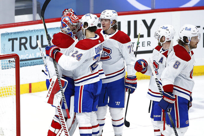 Montreal Canadiens' Phillip Danault (24) and Tyler Toffoli (73) celebrate with goaltender Carey Price (31) the team's win over the Winnipeg Jets in Game 2 of an NHL hockey Stanley Cup second-round playoff series Friday, June 4, 2021, in Winnipeg, Manitoba. (John Woods/The Canadian Press via AP)