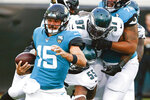 Jacksonville Jaguars quarterback Gardner Minshew (15) tries to scramble from the pocket as he is pressured by Philadelphia Eagles defensive end Brandon Graham (55) and defensive tackle Malik Jackson (97) during the first half of an NFL preseason football game, Thursday, Aug. 15, 2019, in Jacksonville, Fla. (AP Photo/Stephen B. Morton)