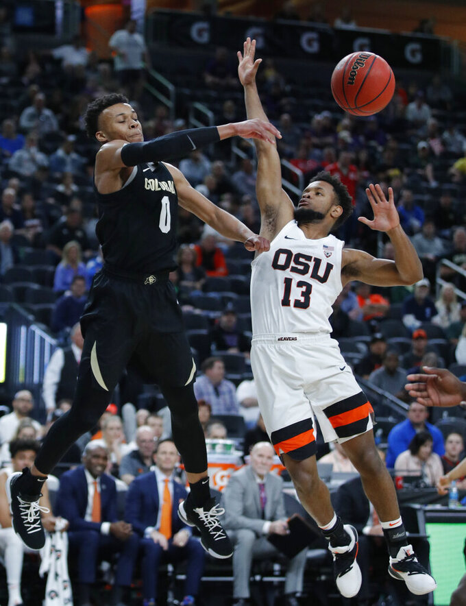 Colorado's Shane Gatling, left, passes around Oregon State's Antoine Vernon during the first half of an NCAA college basketball game in the quarterfinal round of the Pac-12 men's tournament Thursday, March 14, 2019, in Las Vegas. (AP Photo/John Locher)