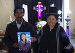 "Celso Vila and Luisa Ticona pose with a photo of their late daughter Mery Vila inside the ""Stairway to Heaven"" funeral home, in La Paz, Bolivia, Thursday, July 11, 2019. Vila's partner killed the 26-year-old woman by striking her several times on the head with a hammer. Vila is one of 69 femicides reported in Bolivia since January, the highest in six years in the same period. (AP Photo/Juan Karita)"