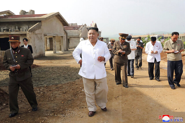In this undated photo provided on Thursday, July 23, 2020 by the North Korean government, North Korean leader Kim Jong Un, center, visits a new chicken farm being built in Hwangju County, North Korea. Independent journalists were not given access to cover the event depicted in this image distributed by the North Korean government. The content of this image is as provided and cannot be independently verified. Korean language watermark on image as provided by source reads: