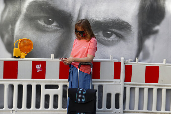 A woman wearing a face mask checks her cellphone downtown in Munich, Germany, Tuesday, Sept. 22, 2020. (AP Photo/Matthias Schrader)