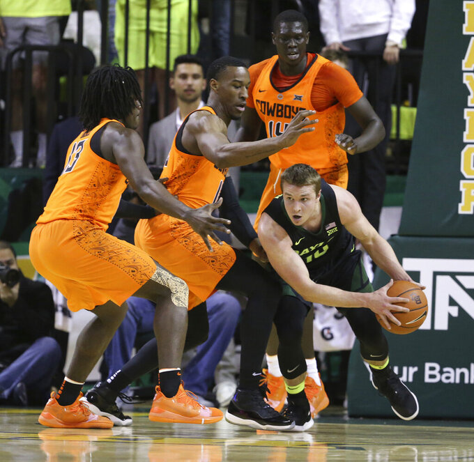 Baylor guard Makai Mason (10) is guarded by Oklahoma State guard Isaac Likekele, left, forward Cameron McGriff, center, and forward Yor Anei, right, in the first half of an NCAA college basketball game, Wednesday, March 6, 2019, in Waco, Texas. (Rod Aydelotte/Waco Tribune-Herald via AP)
