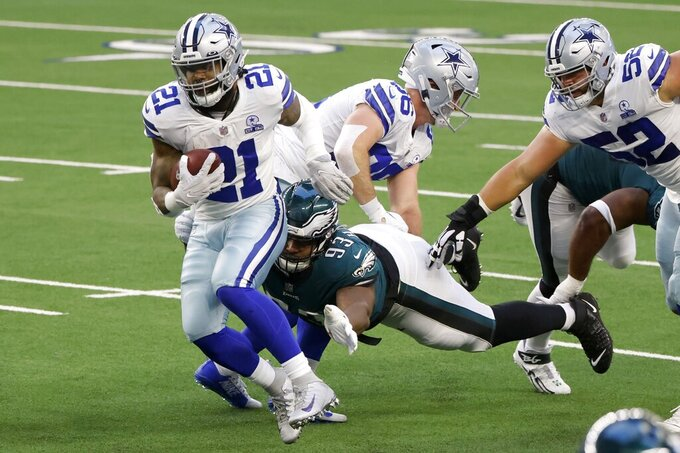 Dallas Cowboys running back Ezekiel Elliott (21) attempts to escape a tackle attempt by Philadelphia Eagles defensive tackle Javon Hargrave (93) in the first half of an NFL football game in Arlington, Texas, Sunday, Dec. 27. 2020. (AP Photo/Ron Jenkins)