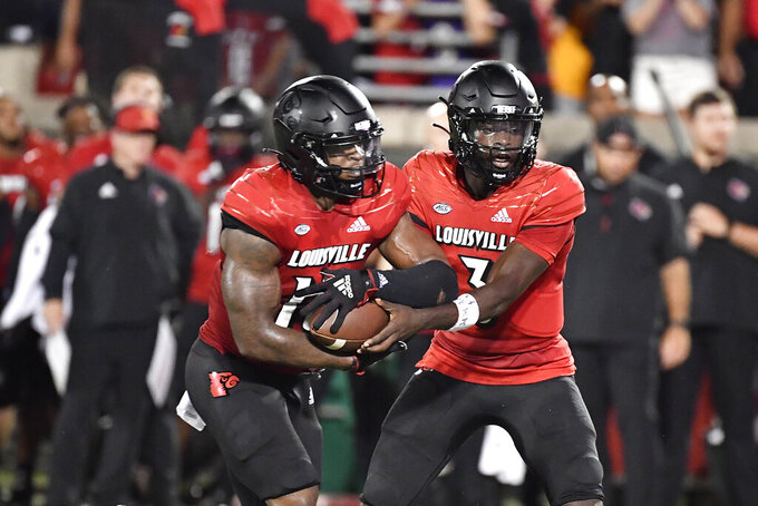 Louisville quarterback Malik Cunningham (3) hands the ball off to running back Jalen Mitchell (15) during the first half of the team's NCAA college football game against Central Florida in Louisville, Ky., Friday, Sept. 17, 2021. (AP Photo/Timothy D. Easley)