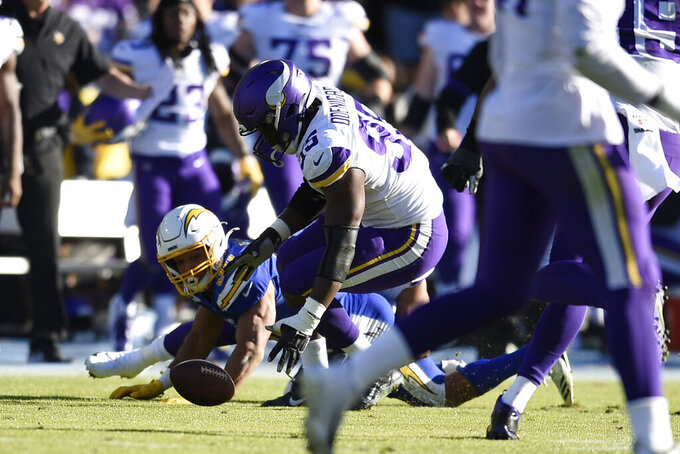 Minnesota Vikings defensive end Ifeadi Odenigbo, center, picks up a fumble before running it back for a touchdown during the first half of an NFL football game against the Los Angeles Chargers, Sunday, Dec. 15, 2019, in Carson, Calif. (AP Photo/Kelvin Kuo)