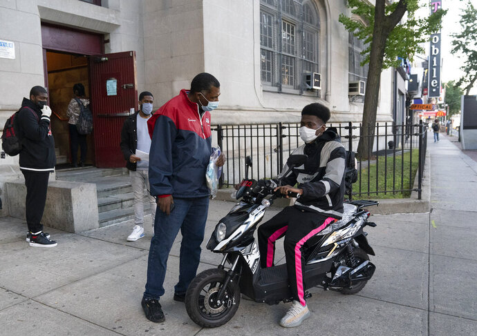School aide Serin Brandt, center, helps a student as he arrives on a scooter for the first day of in-person classes at Erasmus High School in Brooklyn's Flatbush neighborhood, Thursday, Oct. 1, 2020 in New York. The city's plans to send kids back into classrooms rely on an ambitious plan to do random virus testing of pupils and staff throughout the school year. (AP Photo/Mark Lennihan)