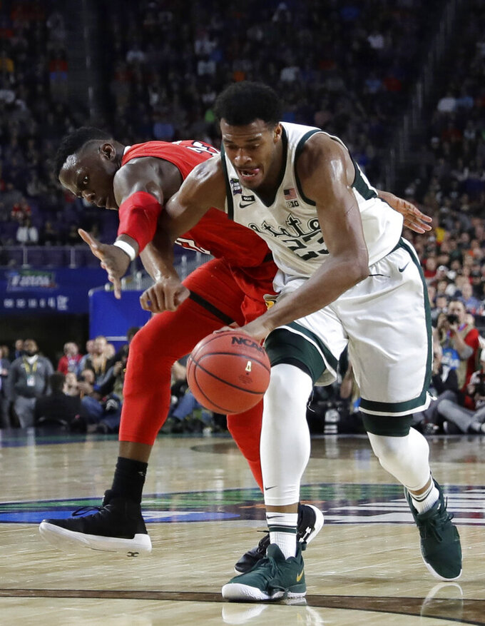 Michigan State forward Xavier Tillman fights for a loose ball with Texas Tech center Norense Odiase, left, during the first half in the semifinals of the Final Four NCAA college basketball tournament, Saturday, April 6, 2019, in Minneapolis. (AP Photo/David J. Phillip)