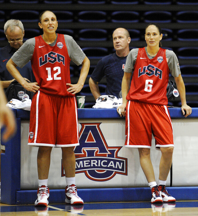 FILE - In this July 14, 2012, file photo, U.S women's Olympic basketball players Diana Taurasi (12) and Sue Bird (6) watch during practice in Washington.  The U.S. women's national basketball team college tour is set to tip off next month. USA Basketball announced Wendesday, Oct. 9, 2019,  that members of the national team will play exhibition games at Stanford, Oregon State, Texas A&M and Oregon in early November to prepare for the upcoming FIBA tournament later next month.  (AP Photo/Nick Wass, File)