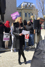 Adult film star Stormy Daniels reads a statement, protesting the Illinois surcharge on live adult entertainment centers, beneath the statue of Abraham Lincoln at the state Capitol, Friday, March 22, 2019 in Springfield, Ill. The actress famous for her alleged affair with Donald Trump before he became president read a two-minute statement before she was whisked off to a local strip club to sign copies of her book. Daniels, whose real name is Stephanie Clifford, says the tax unfairly ties nude dancing to violence against women and that it