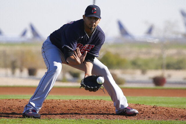 FILE - In this Feb. 13, 2020, file photo, Cleveland Indians starting pitcher Carlos Carrasco fields a grounder during spring training baseball workouts for pitchers and catchers in Avondale, Ariz. Carlos Carrasco felt discomfort in his right leg during a spring training workout and is undergoing imaging tests. The Indians said he will not work out Thursday, Feb. 20, 2020, and the team plans to provide an update on his status and a diagnosis Friday. (AP Photo/Ross D. Franklin, File)