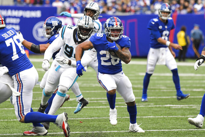 New York Giants' Devontae Booker (28) rushes past Carolina Panthers' Daviyon Nixon (94) during the second half of an NFL football game, Sunday, Oct. 24, 2021, in East Rutherford, N.J. (AP Photo/Bill Kostroun)