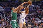 Phoenix Suns forward Kelly Oubre Jr. (3) shoots as Boston Celtics forward Grant Williams defends during the second half of an NBA basketball game, Monday, Nov. 18, 2019, in Phoenix. (AP Photo/Matt York)
