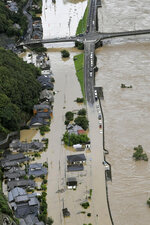 Houses are partially submerged in the Kuma River flooded with heavy rain in Yatsushiro, Kumamoto prefecture, southwestern Japan, Saturday, July 4, 2020. The Japan Meteorological Agency raised the heavy rain warnings in many parts of the prefectures to the highest level shortly before 5 a.m. It was the first time for the agency to do so in the two prefectures, Kumamoto and Kagoshima. (Kyodo News via AP)