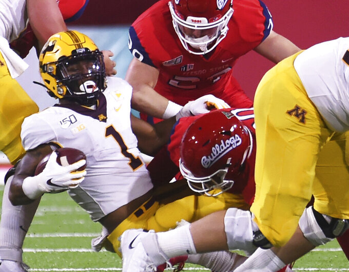 Fresno State's Kevin Atkins, right, with Fresno's Justin Rice, top right, tackles Minnesota's Rodney Smith, left ,during an NCAA college football game Saturday, Sept. 7, 2019, in Fresno, Calif. (Eric Paul Zamora/The Fresno Bee via AP)