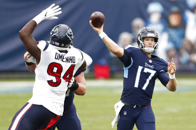 Tennessee Titans quarterback Ryan Tannehill (17) passes as he is pressured by Houston Texans defensive end Charles Omenihu (94) in the first half of an NFL football game Sunday, Oct. 18, 2020, in Nashville, Tenn. (AP Photo/Wade Payne)