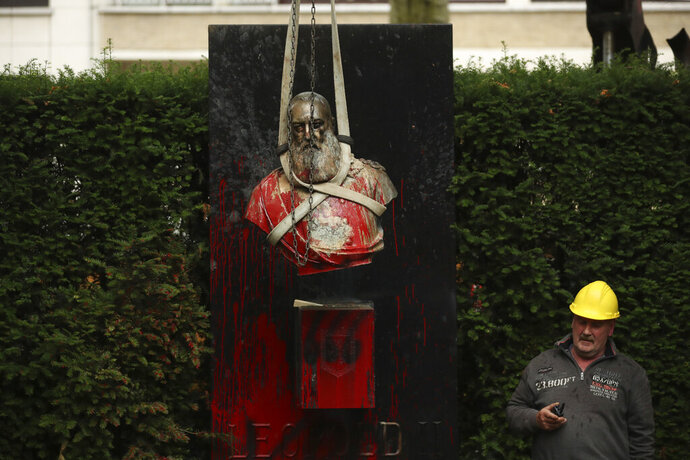 A workman stands by as a bust of Belgium's King Leopold II is hoisted off of its plinth and removed from a park in Ghent, Belgium on Tuesday, June 30, 2020. Protests sweeping the world after George Floyd's death in the U.S. have added fuel to a movement to confront Europe's role in the slave trade and its colonial past. Leopold II is increasingly seen as a stain on the nation where he reigned from 1865 to 1909 with some demonstrators calling for his removal from public view. (AP Photo/Francisco Seco)