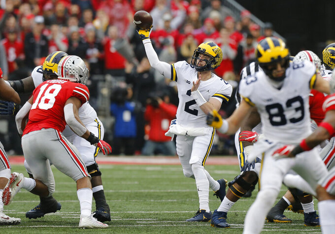 "FILE - In this Nov. 24, 2018, file photo, Michigan quarterback Shea Patterson throws a pass against Ohio State during an NCAA college football game in Columbus, Ohio. Magistrate Judge Norah McCann King moved a change of plea hearing from June 18 to July 1, 2020, for Daniel Rippy. Rippy is accused of making an ""electronic communication"" threat from California during this game between Ohio State and the University of Michigan threatening a shooting and vowing to hurt players on the football team. (AP Photo/Jay LaPrete)"