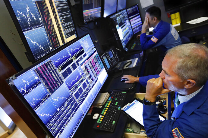 FILE - In this Aug. 5, 2019, file photo trader Timothy Nick, right, works on the floor of the New York Stock Exchange. Mutual fund managers are making the most of the shaky stock market, which has provided them an opportunity to prove themselves and lure back investors who dumped them in recent years. Nearly half of all actively managed U.S. stock funds turned in better returns than their average index-fund peer for the 12 months through June, according to fund tracker Morningstar. (AP Photo/Richard Drew, File)