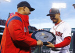 FILE - In this April 11, 2019, file photo, Boston Red Sox manager Alex Cora, left, presents right fielder Mookie Betts with the 2018 AL MVP Award before a baseball game between the Red Sox and the Toronto Blue Jays at Fenway Park in Boston. The award includes the name and image of Kenesaw Mountain Landis. A group of House Democrats called Tuesday, Aug. 4, 2020, for the name of former baseball commissioner Landis to be pulled off future Most Valuable Player plaques. (AP Photo/Winslow Townson, File)