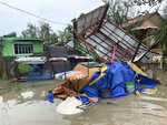 The remains of a barbershop is surrounded by floods in Pola town on the island of Mindoro, central Philippines, Monday, Oct. 26, 2020. A fast-moving typhoon forced thousands of villagers to flee to safety in provinces south of the Philippine capital Monday, flooding rural villages and ripping off roofs, officials said. (AP Photo/Erik De Castro)
