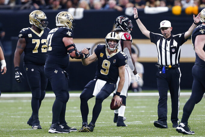 New Orleans Saints quarterback Drew Brees (9) is helped up by offensive tackle Ryan Ramczyk (71) after being sacked in the second half of an NFL football game against the Atlanta Falcons in New Orleans, Sunday, Nov. 10, 2019. (AP Photo/Butch Dill)