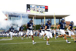 FILE - In this Sept. 6, 2019, file photo, Rice University football players run onto the field for an NCAA football game in Houston.  The Wild West nature of the upcoming college football season can be illustrated in part by 160 miles of Texas highway that connects the trendy college city of Austin with the bustling metropolis of Houston. (AP Photo/Matt Patterson, File)