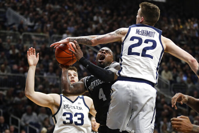 Butler forward Sean McDermott (22) fouls Providence guard Maliek White (4) as he shoos in the second half of an NCAA college basketball game in Indianapolis, Saturday, Feb. 1, 2020. Providence defeated Butler 65-61. (AP Photo/Michael Conroy)
