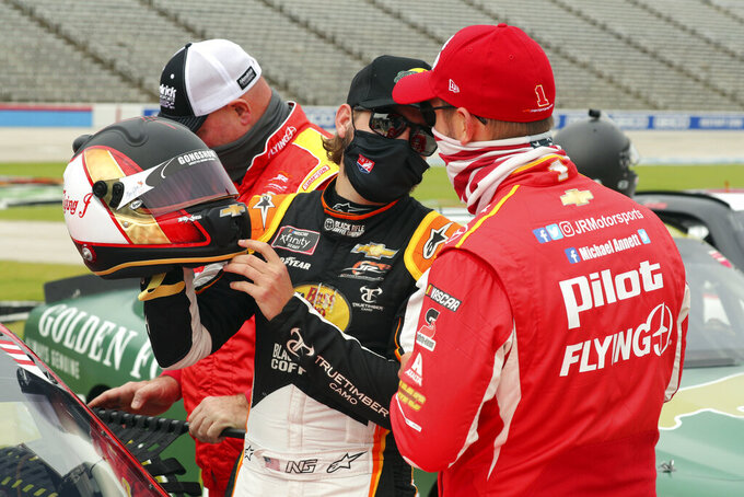 NASCAR Xfinity Series driver Noah Gragson (9) checks out the helmet of driver Michael Annett (1) before a NASCAR Xfinity Series auto race at Texas Motor Speedway in Fort Worth, Texas, Saturday Oct. 24, 2020. (AP Photo/Richard W. Rodriguez)
