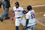 Cleveland Indians' Carlos Santana, left, is congratulated by Roberto Perez while scoring from third base on a sacrifice fly by Oscar Mercado off Minnesota Twins pitcher Rich Hill in the fourth inning of a baseball game Saturday, Sept. 12, 2020, in Minneapolis. (AP Photo/Jim Mone)