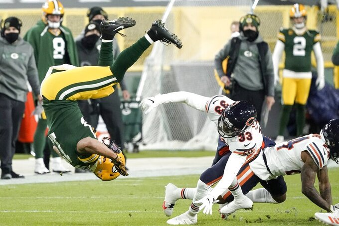 Green Bay Packers' Aaron Jones is tripped up by Chicago Bears' Jaylon Johnson after catching a pass during the first half of an NFL football game Sunday, Nov. 29, 2020, in Green Bay, Wis. (AP Photo/Morry Gash)
