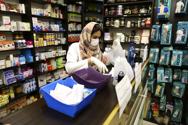 A pharmacist wearing a face masks works in western Tehran, Iran, Saturday, Feb. 29, 2020. Iran is preparing for the possibility of