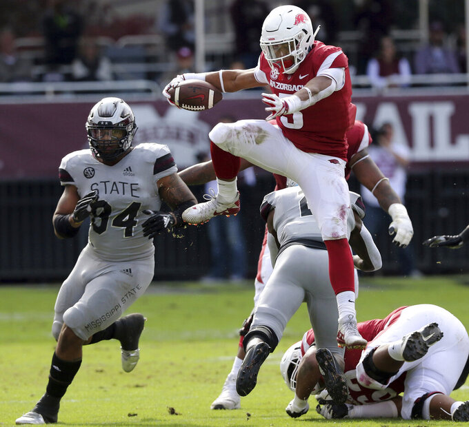 FILE - In this Nov. 17, 2018, file photo, Arkansas running back Rakeem Boyd (5) hurdles a Mississippi State player on his way to a first down during the first half of an NCAA college football game in Starkville, Miss. Head coach Chad Morris, who made a collegiate name for himself coaching high-powered offenses at Tulsa and Clemson before taking head man duties at Southern Methodist in 2015, never found himself a reliable offensive threat with the Razorbacks. The best hope for a breakout may be Boyd. (AP Photo/Jim Lyle, File)
