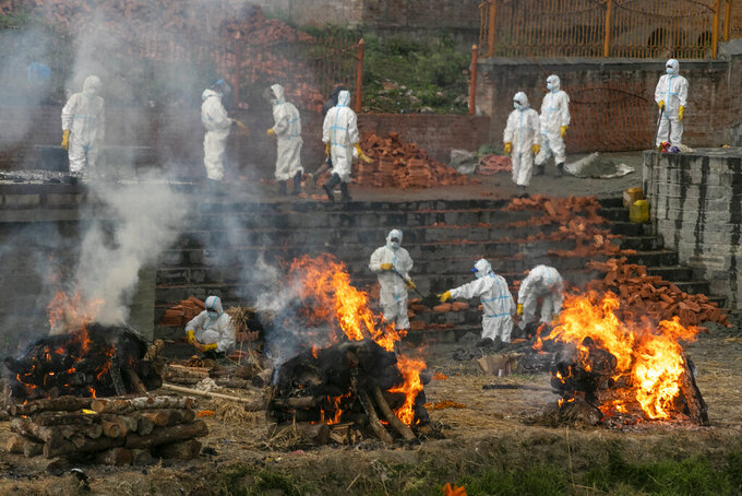 FILE - In this May 5, 2021, file photo, Nepalese men in personal protective suits cremate the bodies of COVID-19 victims while others extend the crematorium as the number of deaths rise near Pashupatinath temple in Kathmandu, Nepal. Authorities extended a lockdown in the capital Kathmandu and surrounding districts by another week as the Himalayan nation recorded the highest COVID-19 daily infections and deaths. (AP Photo/Niranjan Shrestha, File)