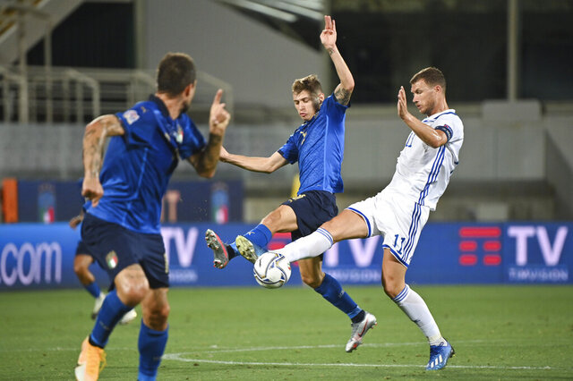 Bosnia Herzegovina's Edin Dzeko, right, and Italy's  Nicolo Barella vie for the ball during the UEFA Nations League soccer match between Italy and Bosnia Herzegovina, at the Artemio Franchi Stadium in Florence, Italy, Friday, Sept. 4, 2020. (Massimo Paolone/LaPresse via AP)
